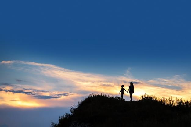 Sylwetki dwojga dzieci o zachodzie słońca. dzieci trzymają się za ręce. piękny zachód słońca.