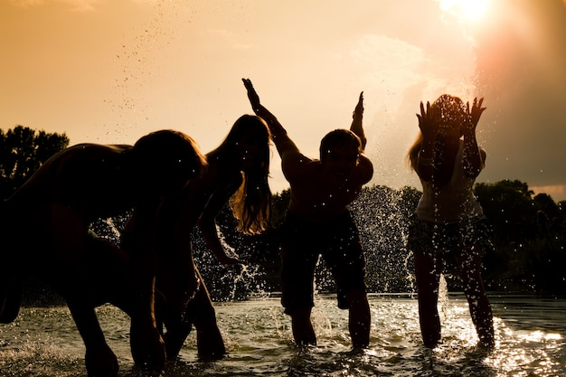 Sylwetki dziewcząt bawiące się w wodzie przed słońcem