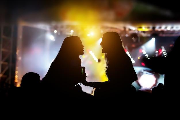 Sylwetki dziewcząt na pokazie muzyki na świeżym powietrzu.