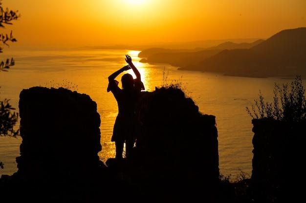 Sylwetki dziewczyny na tle morza i zachodzącego słońca