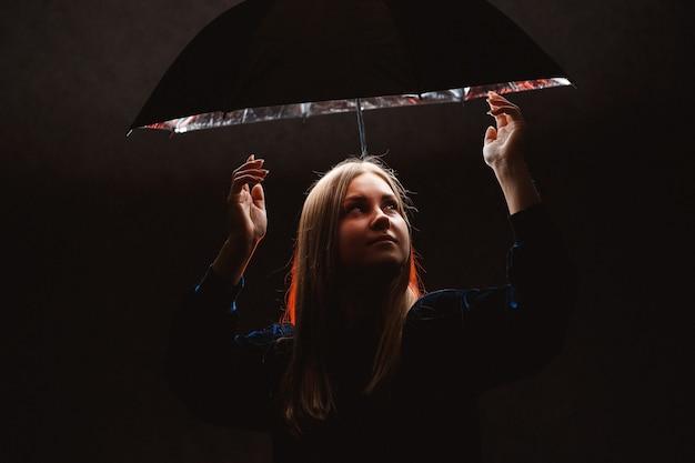 Sylwetki dziewczyny pod parasolem w ciemnym świetle