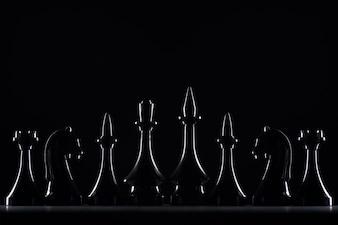 Sylwetki figury szachowe na białym tle na czarno, koncepcja biznesowa