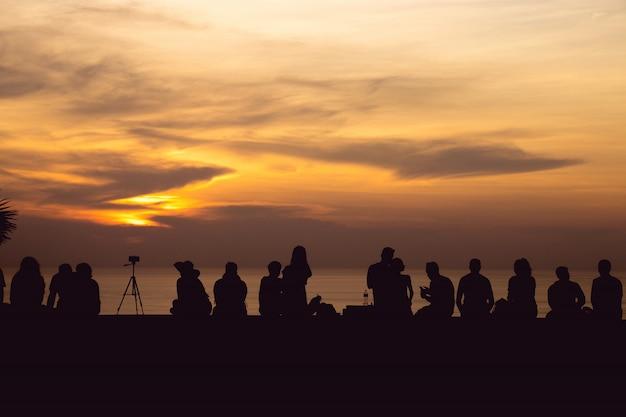 Sylwetki grupy ludzi siedzi spojrzenie przy zmierzchem zaświeca z pomarańczowym niebem przy phuket, tajlandia