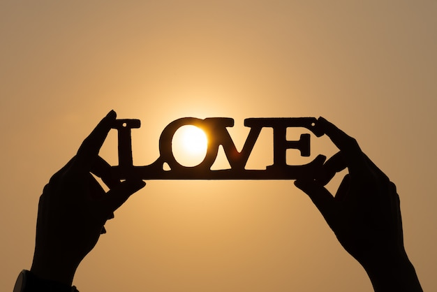 Sylwetki kobieta wręcza trzymać słowo miłości przy zmierzch ścianą