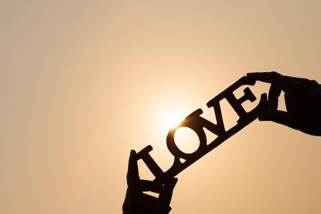 Sylwetki kobieta wręcza trzymać słowo miłości przy zmierzchem. koncepcje miłosne.