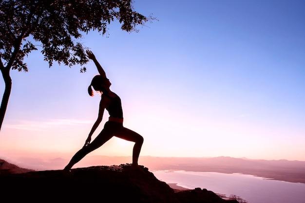Sylwetki kobieta z joga posturą na górze przy zmierzchem.