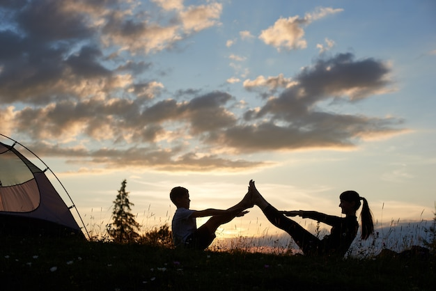 Sylwetki kobiety i chłopca siedzącego na trawie z kwiatami i robi rozciąganie o wschodzie słońca w pobliżu kempingu. szczęśliwe twarze matki i dziecka podczas uprawiania sportów pod porannym niebem