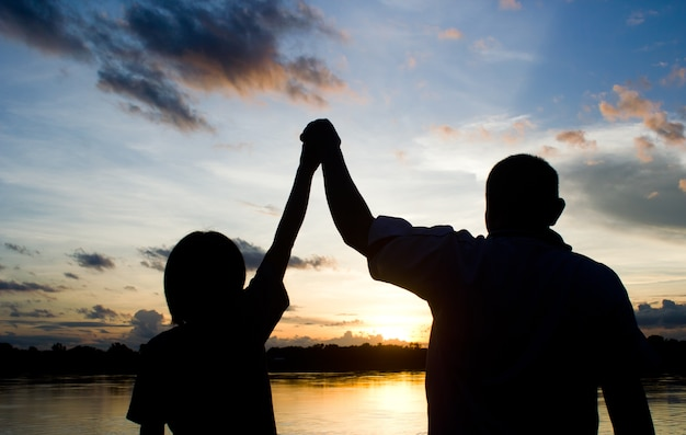 Sylwetki kobiety i fatman pokazać swoje ręce, aby winer podpisać piękne słońce ustawić tło.