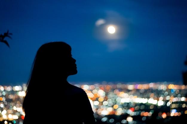 Sylwetki kobiety portret z księżyc w pełni w miasto nocy światła bokeh tle