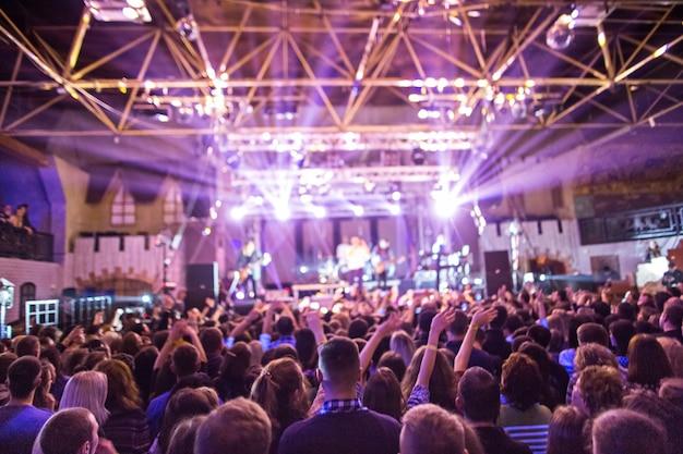 Sylwetki koncertowego tłumu przed jasnymi światłami scenicznymi. koncert abstrakcyjnego zespołu rockowego