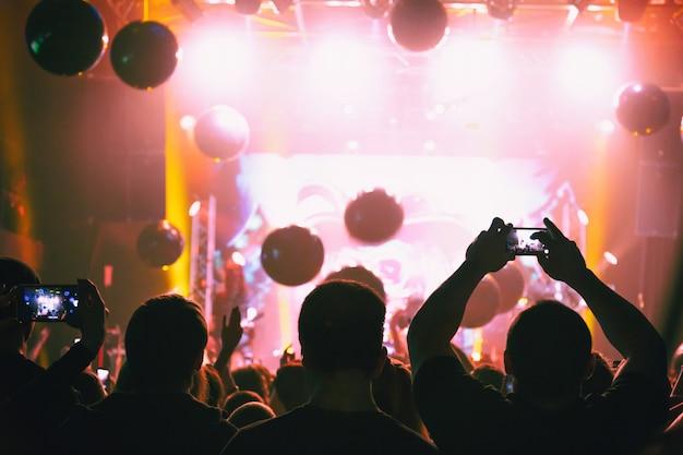 Sylwetki koncertowego tłumu ze smartfonami w rękach