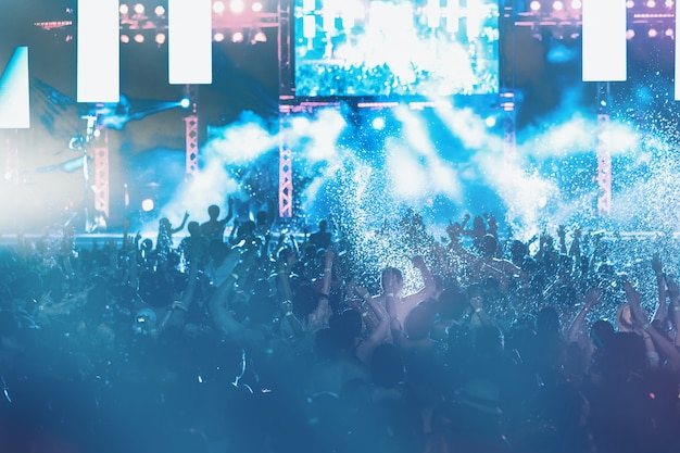 Sylwetki koncertowy tłum przed jaskrawymi scenicznymi światłami, basenu przyjęcie