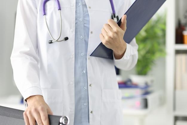 Sylwetki lekarza posiadającego schowek w gabinecie lekarskim. pojęcie opieki medycznej