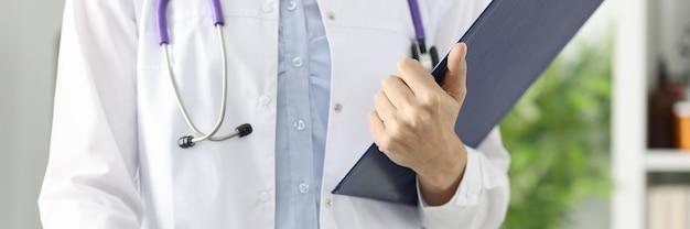 Sylwetki lekarza trzymającego schowek w koncepcji opieki medycznej w gabinecie medycznym
