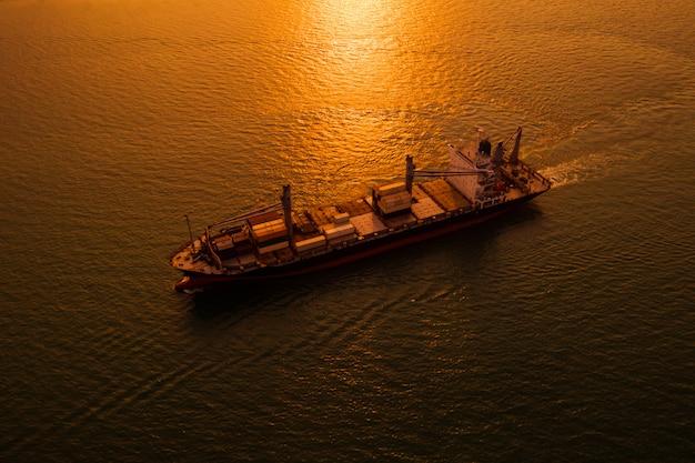 Sylwetki logistyki wysyła ładunek otwarte morze nad zmierzchu tłem i
