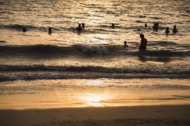 Sylwetki ludzi fala morze plaża zachód