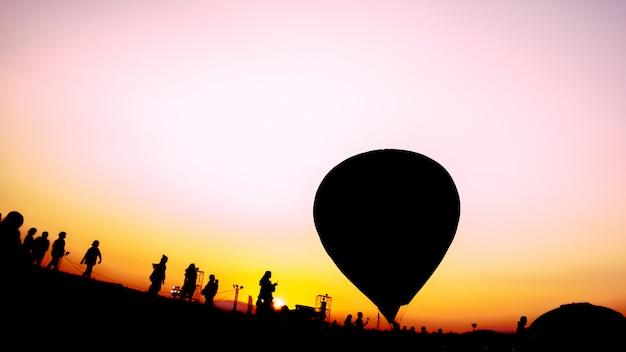 Sylwetki ludzi i balonów na ogrzane powietrze na festiwalu balonowym
