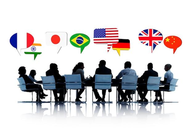 Sylwetki ludzi na spotkaniu rozmawiających o różnych krajach