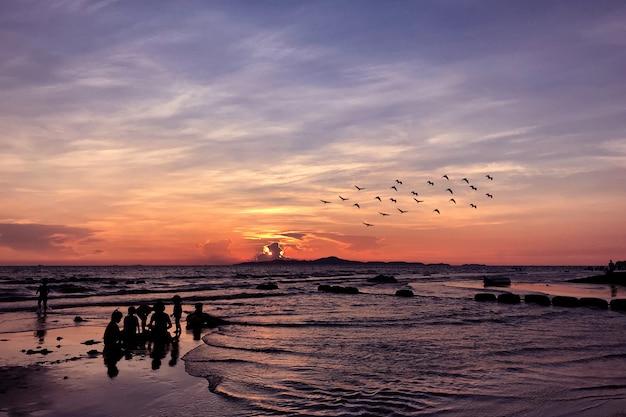 Sylwetki ludzi na tropikalnej plaży w godzinach wieczornych.
