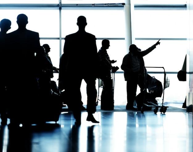 Sylwetki ludzi podróżujących na lotnisku