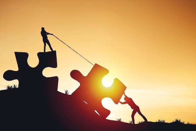 Sylwetki ludzi pomagających połączyć układankę i puzzle do sukcesu