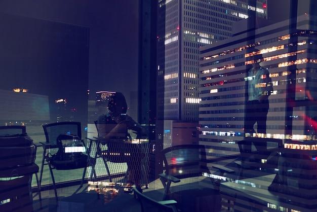 Sylwetki ludzi przy pracy w biurze w nocy