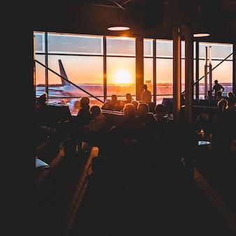 Sylwetki ludzi siedzących na krześle w pobliżu okna podczas zachodu słońca