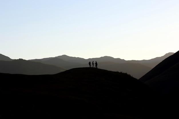 Sylwetki ludzi stojących na zboczu wzgórza