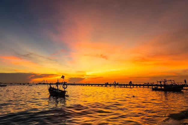 Sylwetki mała łódź rybacka przy brzeg w zmierzchu przy uderzenia phra plażą, sriracha choburi, thailand
