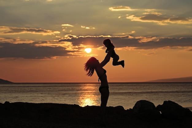 Sylwetki matki i dziecka bawi się na plaży w pobliżu wody morskiej lub oceanicznej wieczorem lub o zmierzchu w letni dzień na naturalny