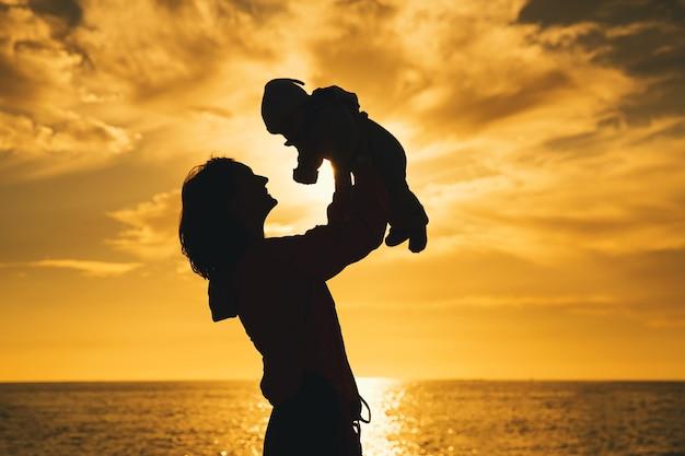 Sylwetki matki i dziecka o zachodzie słońca na plaży oceanu latem szczęśliwa rodzina w tle