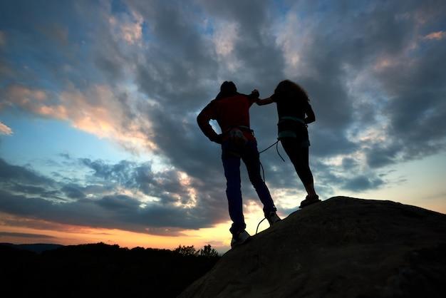 Sylwetki mężczyzny i kobiety patrzą na zachód słońca na szczycie skały. wycieczkowicze dobierają się na dramatycznym niebie przy zmierzchem. widok z tyłu.