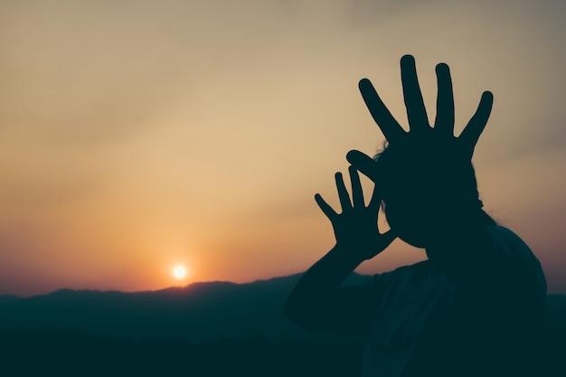 Sylwetki młoda dziewczyna z jej ręką przedłużyć sygnalizuje zatrzymywać przy zmierzchu czasem