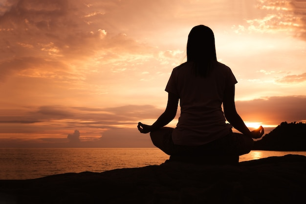 Sylwetki młodej azjatykciej kobiety ćwiczy joga