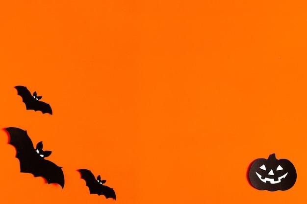 Sylwetki nietoperzy z czarnego papieru na pomarańczowym tle na halloween