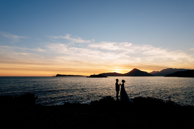 Sylwetki nowożeńców stoją trzymając się za ręce na plaży w pobliżu morza na tle zachodu słońca