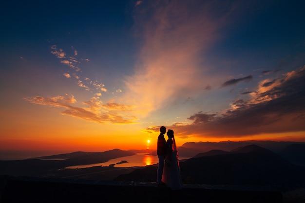 Sylwetki o zachodzie słońca na górze lovcen