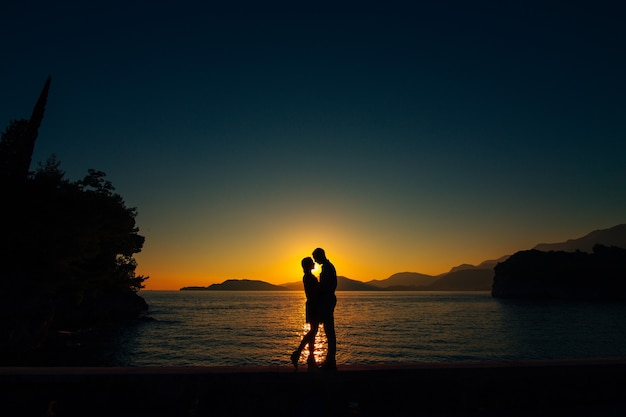 Sylwetki o zachodzie słońca na plaży