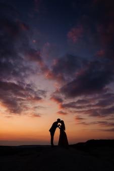 Sylwetki panny młodej i pana młodego, nowożeńcy patrzą na siebie, trzymając się za ręce i całując. koncepcja fotografii ślubnej. kopia przestrzeń