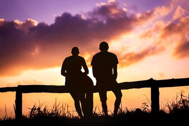 Sylwetki pary kochanek z góra krajobrazem w pięknym zmierzchu niebie