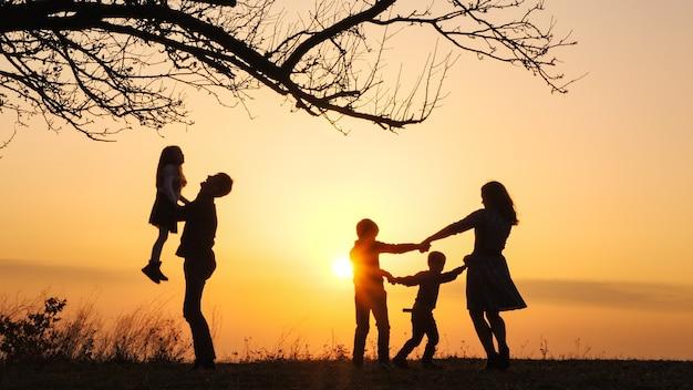 Sylwetki rodziny spędzającej razem czas na pobliskiej łące podczas zachodu słońca