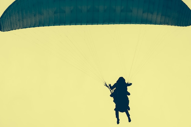 Sylwetki skoczków na żółtym niebie