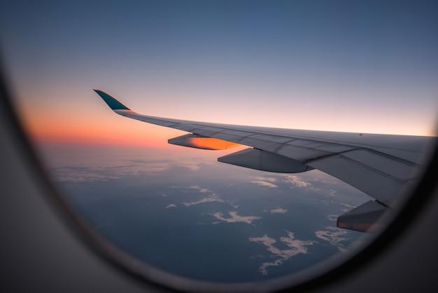 Sylwetki skrzydło samolot przy wschodu słońca widokiem przez okno.
