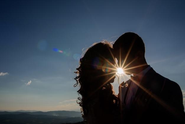Sylwetki ślubu pary pozycja w promieniach słońce przed góra krajobrazem