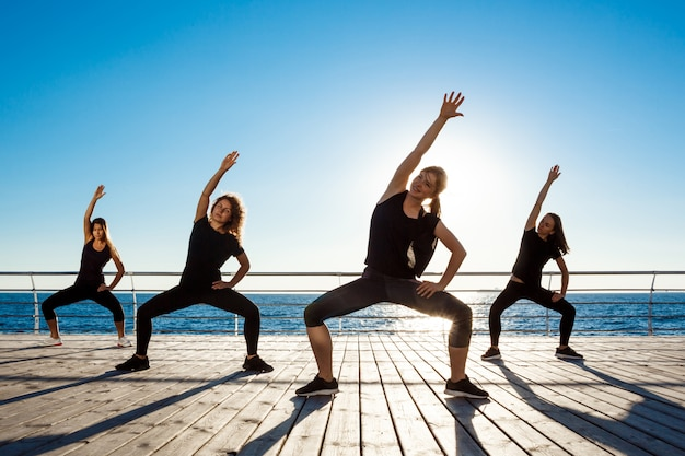 Sylwetki sportowej kobiety tańczy zumba w pobliżu morza o wschodzie słońca