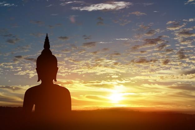 Sylwetki statua buddha przy zmierzchu tłem