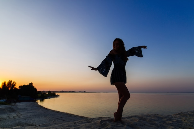 Sylwetki szczupła kobieta pozuje na piaskowatej plaży. młoda kobieta samotności cieszy się zachód słońca na piaszczystej plaży. piękna dziewczyna spaceru w zachodzie słońca na świeżym powietrzu