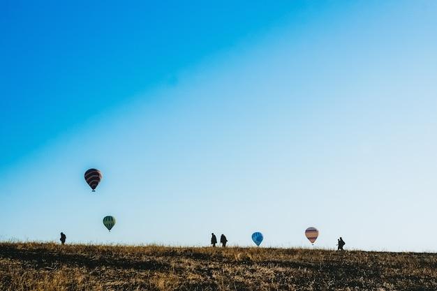 Sylwetki turystów idących przez łąkę podczas oglądania balonów na ogrzane powietrze