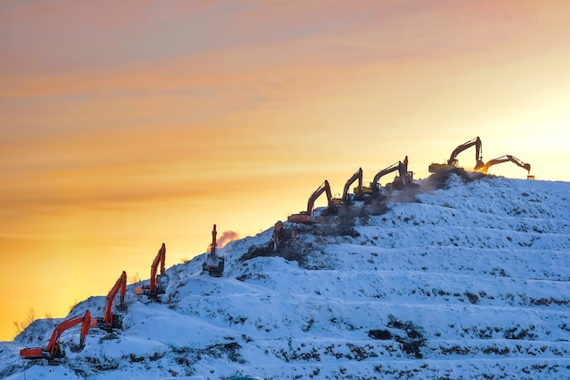 Sylwetki wielu koparek pracujących na ogromnej górze na wysypisku śmieci, pomarańczowym wschodzie lub zachodzie słońca na niebie zimą.