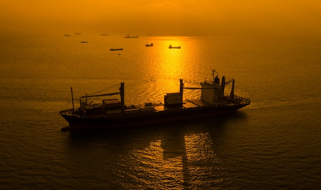 Sylwetki wysyłki ładunku zbiorniki na morzu i wschodu słońca tle